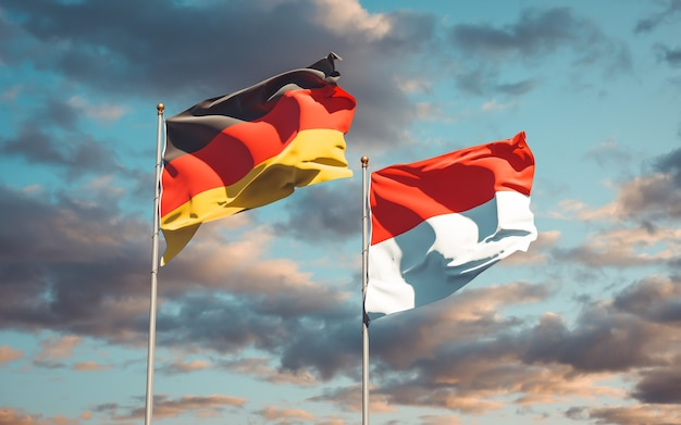 Piękne flagi państwowe niemiec i indonezji razem na błękitnym niebie