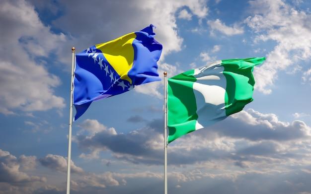Piękne flagi państwowe nigerii oraz bośni i hercegowiny razem na błękitnym niebie