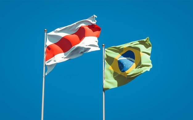 Piękne flagi państwowe nowej białorusi i brazylii razem na błękitne niebo