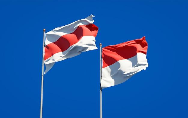 Piękne flagi państwowe nowej białorusi i indonezji razem na błękitnym niebie