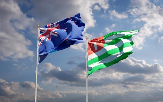 Piękne flagi państwowe nowej zelandii i abchazji razem na błękitnym niebie. grafika 3d