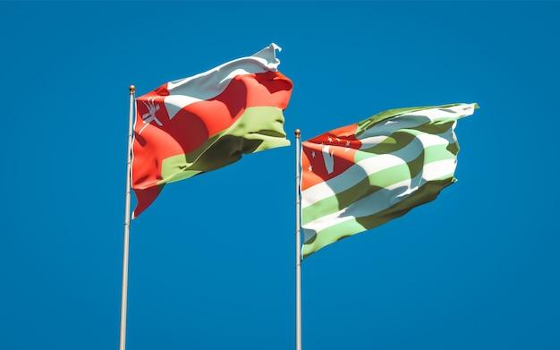 Piękne flagi państwowe omanu i abchazji razem na błękitnym niebie. grafika 3d