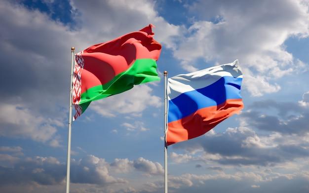 Piękne flagi państwowe rosji i białorusi razem na błękitnym niebie. grafika 3d