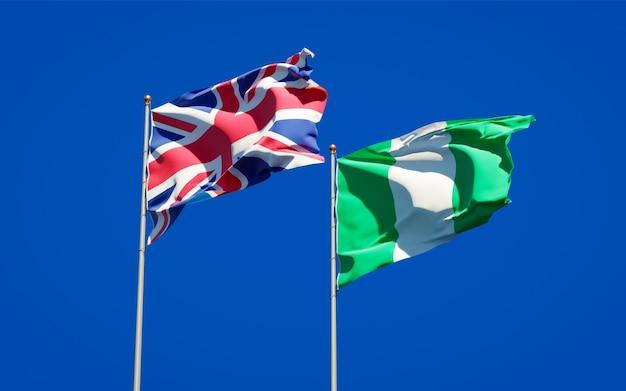 Piękne flagi państwowe wielkiej brytanii i nigerii razem na błękitnym niebie