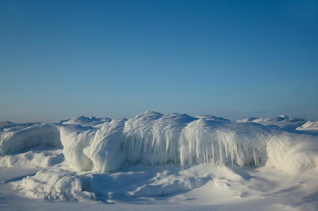 Piękne formacje lodowe ze śniegiem wzdłuż wybrzeża na błękitne niebo, zimowy krajobraz