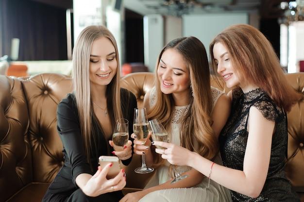 Piękne gorące dziewczyny bawią się na imprezie, piją szampana.