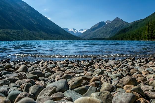 Piękne górskie jezioro z turkusowym multinskoe. czysta woda w republice ałtaju syberia rosja. wieczorny krajobraz górski z jeziorem z przezroczystą wodą na pierwszym planie