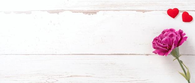 Piękne goździki i kształt serca z białą pustą kartą izolowaną na jasnym drewnianym stole, miejsce do kopiowania, układanie płaskie, widok z góry, makieta