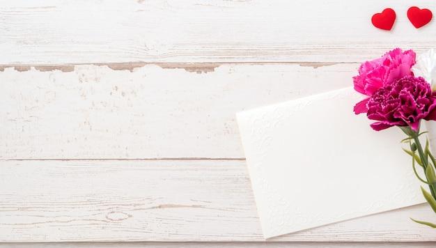 Piękne goździki i kształt serca z białą pustą kartą na białym tle na jasnym drewnianym stole, kopia przestrzeń, płaski układ, widok z góry