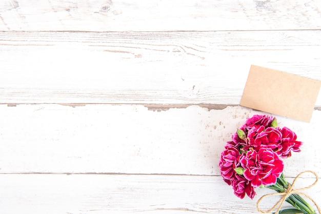 Piękne goździki z szablonem karty na białym tle na jasnym drewnianym stole, kopia przestrzeń, leżał płasko, widok z góry