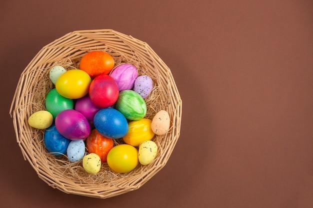Piękne grupowe pisanki na wiosnę wielkanocy, jaja czerwone, niebieskie, fioletowe i żółte w drewnianym koszu
