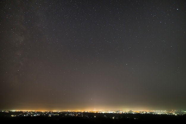 Piękne gwiaździste ciemne nocne niebo nad nowoczesnym miastem