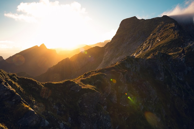 Piękne horyzontalne ujęcie wschodzącego słońca i wysokich skalistych gór pod zachmurzonym niebem