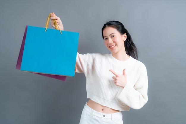 Piękne i młode kobiety azjatyckie gospodarstwa torby na zakupy na szarej ścianie