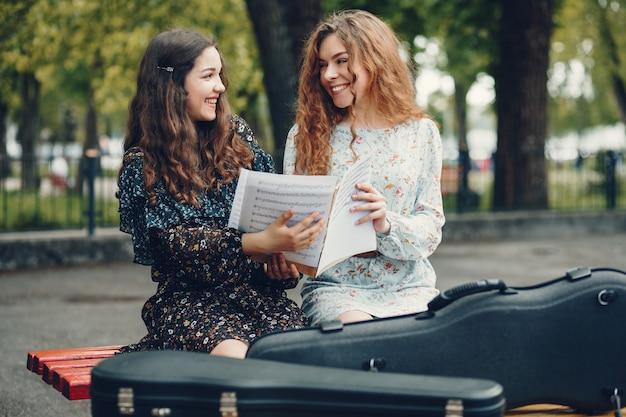 Piękne i romantyczne dziewczyny w parku ze skrzypcami