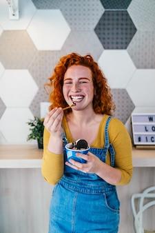 Piękne i szczęśliwe brązowe włosy kobieta korzystających z jedzenia pysznych lodów ręcznie.