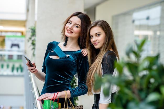 Piękne i szczęśliwe dziewczyny robią zakupy w centrum handlowym.