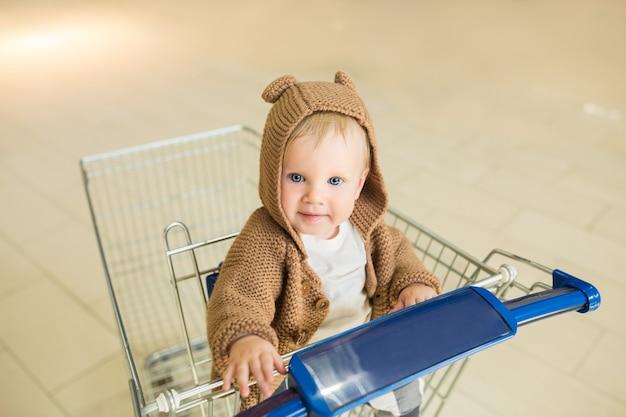 Piękne i urocze dziecko w koszyku - wózek patrzy w kamerę i prosi o zakup. małe dziecko o niebieskich oczach robi zakupy i ciągnie za ręce