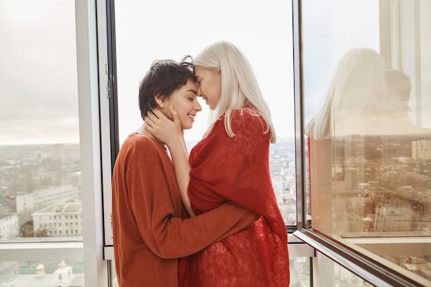 Piękne i urocze kobiety w związku, całujące się i przytulające przy otwartym oknie, stojąc na balkonie