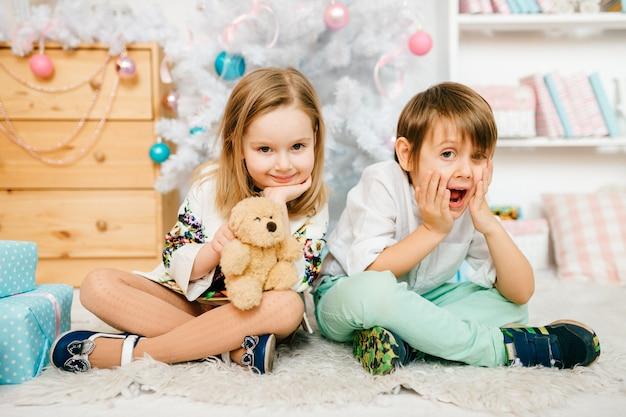 Piękne i zabawne dzieciaki pozuje do aparatu w pokoju z noworocznymi dekoracjami.
