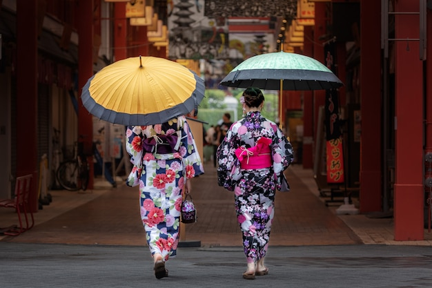 Piękne japońskie dziewczyny w kimono iz parasolem.