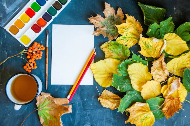Piękne jesienne liście, pędzle, farby i prześcieradło na ciemno