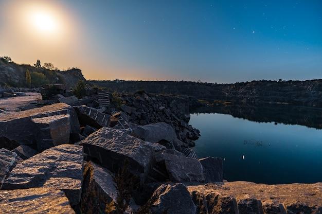 Piękne jezioro otoczone dużymi stosami kamiennych odpadów z ciężkiej pracy w kopalni na tle pięknego nocnego nieba z gwiazdami