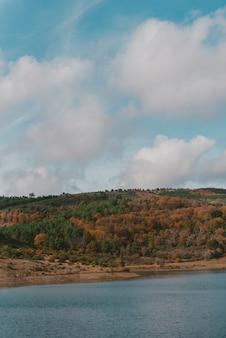 Piękne jezioro otoczone pasmem górskim pod zapierającym dech w piersiach pochmurnym niebem