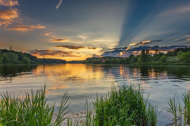 Piękne jezioro otoczone trawą, lasami i kolorowym złotym zachodem słońca