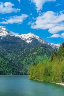 Piękne jezioro ritsa w górach kaukazu. zieleni halni wzgórza, niebieskie niebo z chmurami. wiosenny krajobraz.