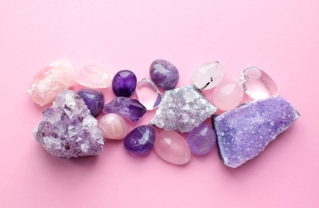 Piękne kamienie szlachetne i druzy z naturalnego fioletowego ametystu mineralnego na różowym tle. ametysty i kwarc różowy. duże kryształy kamieni półszlachetnych.