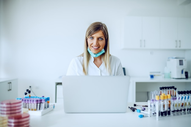 Piękne kaukaski kobiece blond asystentka w laboratorium siedzi przy biurku i za pomocą laptopa do wprowadzania danych.