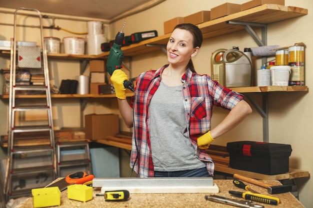 Piękne kaukaski młoda kobieta brązowe włosy w koszulę w kratę i szarą koszulkę, pracując w warsztacie stolarskim przy stole, wiercąc z otworami w kawałku żelaza i drewna podczas robienia mebli.