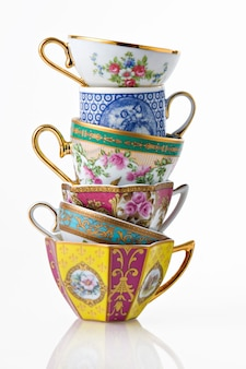 Piękne klasyczne angielskie herbaty i filiżanki kawy tworzące wieżę, odizolowane na białym.