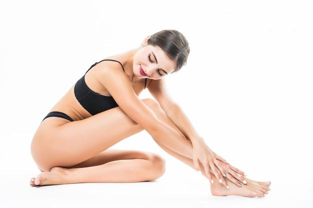 Piękne kobiece ciało na białym tle nad białą ścianą. siedząc na podłodze dotykaj nogi ręką, koncepcja pielęgnacji urody i skóry.