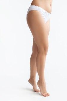 Piękne kobiece ciało w bieliźnie na białym tle.