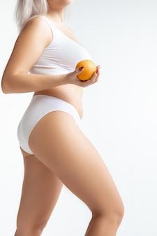 Piękne kobiece ciało w bieliźnie, trzymając pomarańczowy na białym tle na białej ścianie