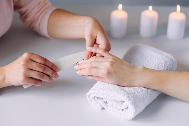 Piękne kobiece dłonie o manicure spa w salonie kosmetycznym. poleruje paznokcie za pomocą pilników do paznokci.