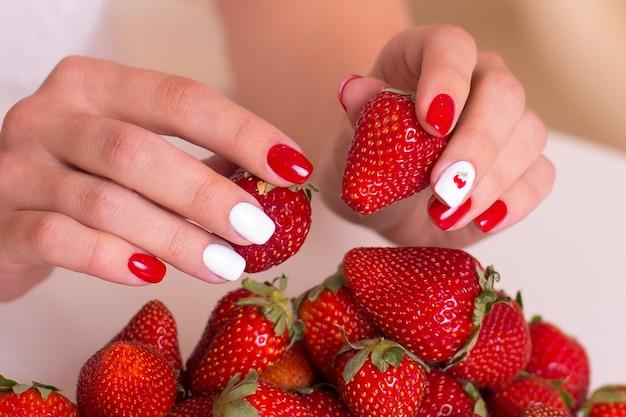 Piękne kobiece dłonie z czerwonymi paznokciami do manicure, trzymające świeże truskawki