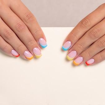 Piękne kobiece dłonie z kolorowymi paznokciami do manicure z tęczowym wzorem