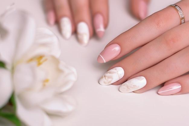 Piękne kobiece dłonie z luksusowymi paznokciami manicure różowy i biały lakier hybrydowy