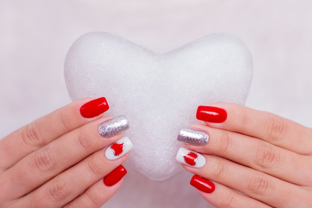 Piękne kobiece dłonie z paznokci czerwony manicure, trzymając mrożone serce