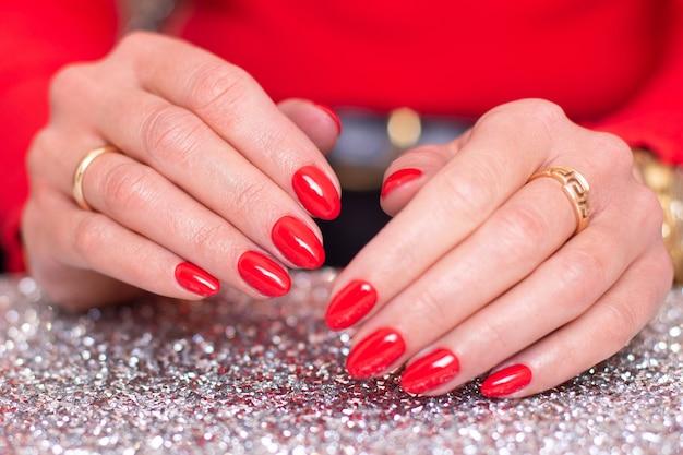 Piękne kobiece dłonie z paznokci czerwony manicure