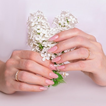 Piękne kobiece dłonie z paznokciami manicure różowy lakier hybrydowy i białe kwiaty