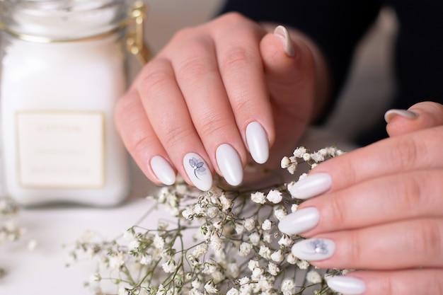 Piękne kobiece dłonie z romantycznymi paznokciami do manicure, żelowy lakier nude ze srebrnym kwiatkiem
