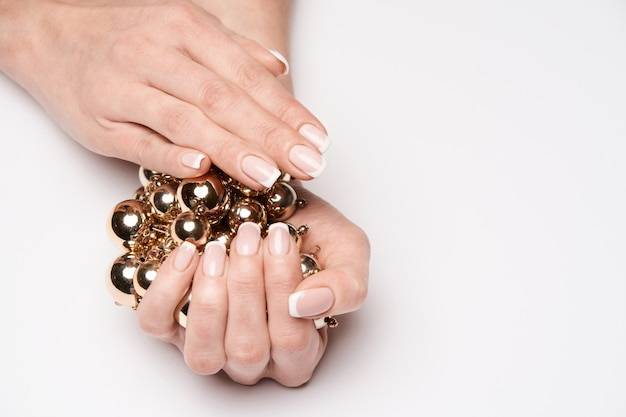 Piękne kobiece dłonie zadbane z francuski manicure trzymając naszyjnik na jasnej powierzchni