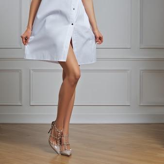Piękne kobiece nagie nogi w ubraniach lekarza.