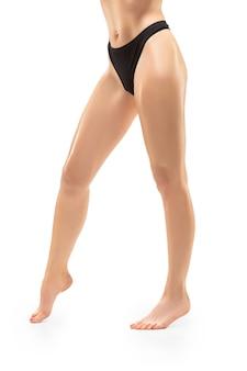 Piękne kobiece nogi, dopasowane ciało na białym tle