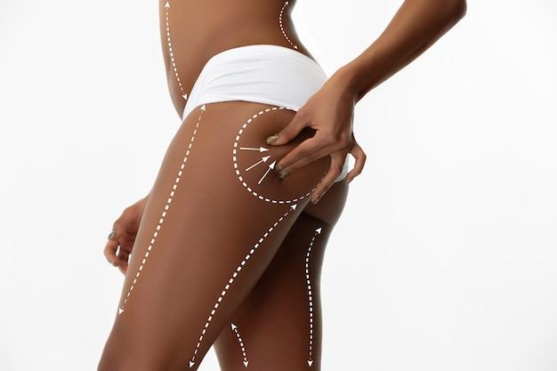 Piękne kobiece nogi i biodra na białym tle. uroda, kosmetyka, spa, depilacja, leczenie i fitness. wysportowana i wysportowana, zmysłowa. pielęgnacja ciała i lifting, linie korekcyjne.