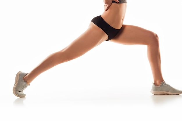 Piękne kobiece nogi i brzuch na białej ścianie. koncepcja uroda, kosmetyki, spa, depilacja, leczenie i fitness. wysportowane i wysportowane, zmysłowe body o zadbanej skórze w bieliźnie. trening.